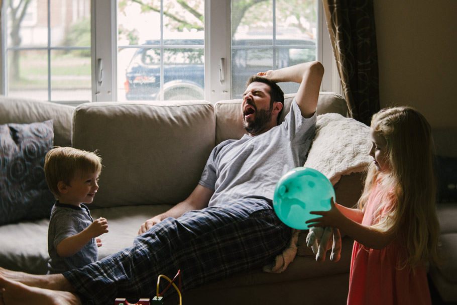 Dad on couch feeling sleepy around kids