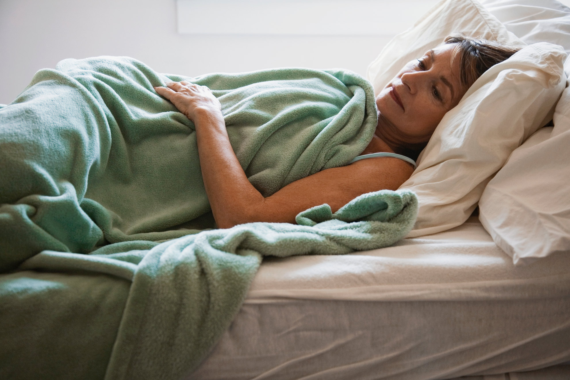 woman with insomnia trying to sleep in bed