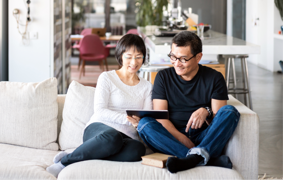 A couple sits on their living room couch, looking at a tablet