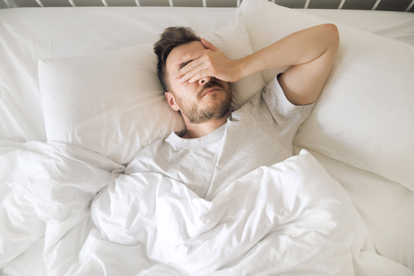 Man laying in white bed sheets with hand over his face